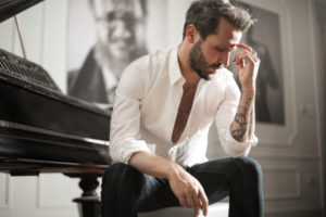 dramatic-tattooed-male-sitting-at-piano-3760269
